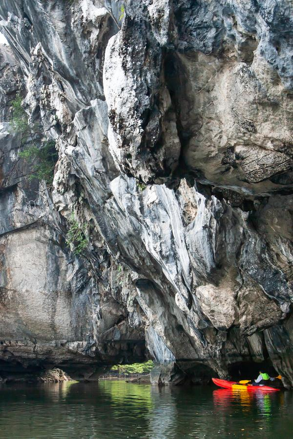 Ontdekkingsreizigermens in reddingsvest het kayaking voor de steile kalksteenklip in het overzees stock afbeelding
