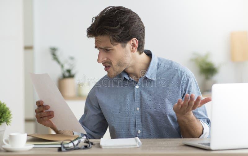 Ontevreden man die belastingaangifte leest bij laptop in dienst royalty-vrije stock afbeelding