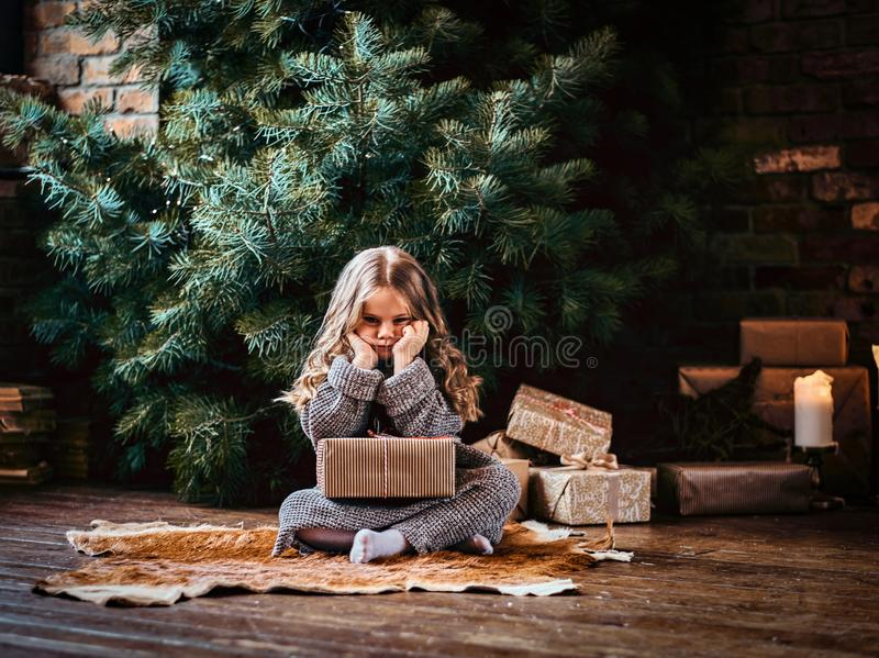 Ontevreden meisje met blonde krullend haar die een warme die sweaterzitting op een vloer dragen door giften wordt omringd naast stock afbeeldingen