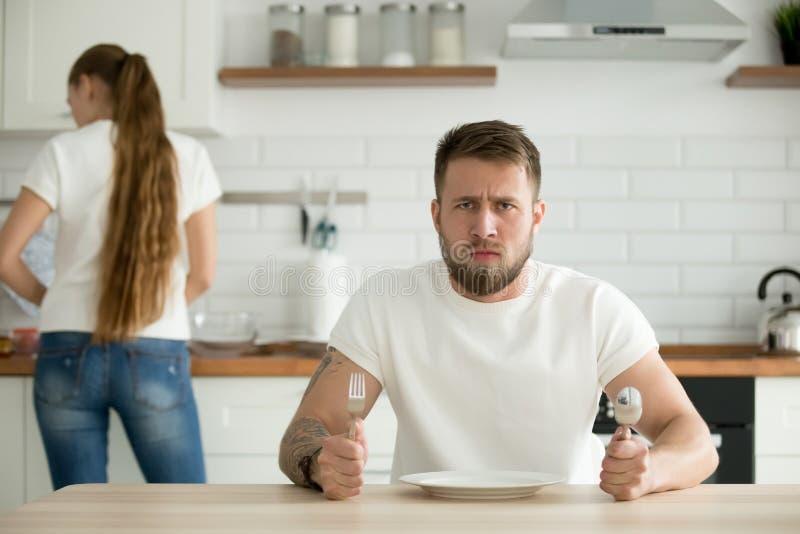 Ontevreden mens die die op diner wachten door vrouw wordt gekookt stock fotografie