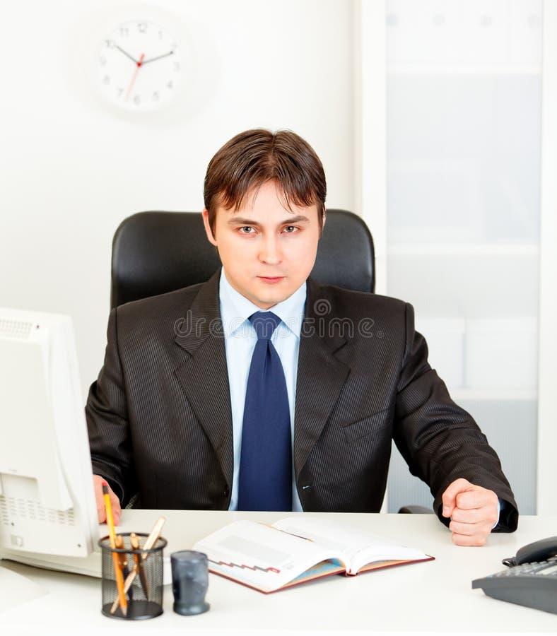Ontevreden zakenman bonzende vuist op lijst stock fotografie