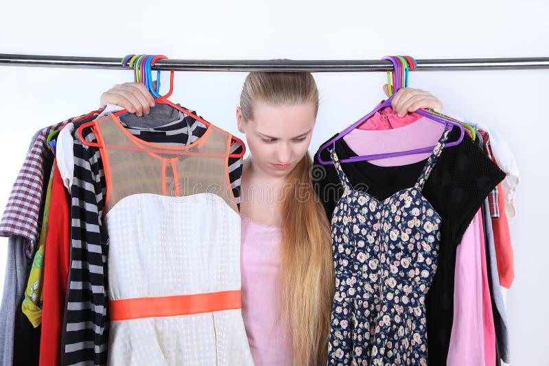 Ontgoocheld meisje die zich dichtbij de hangers met kleren bevinden stock foto's