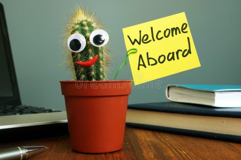 Onthaal aan boord van concept Grappige cactus op werkplaats in het bureau royalty-vrije stock afbeelding