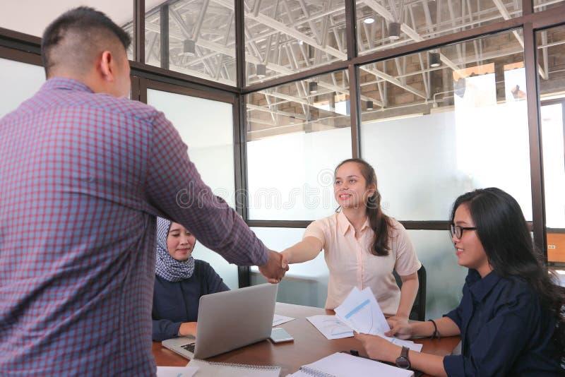 Onthaal aan team! mannen die handen schudden aan vrouw en elkaar met glimlach terwijl hun medewerkers die de zaken bekijken zitte royalty-vrije stock foto