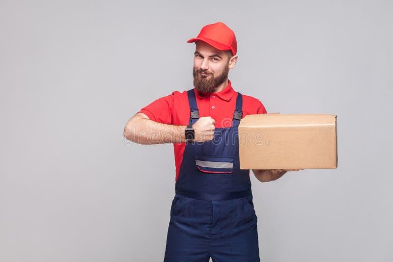Ontime leveringsdienst! Jonge logistische mens met baard in blauw u royalty-vrije stock afbeeldingen