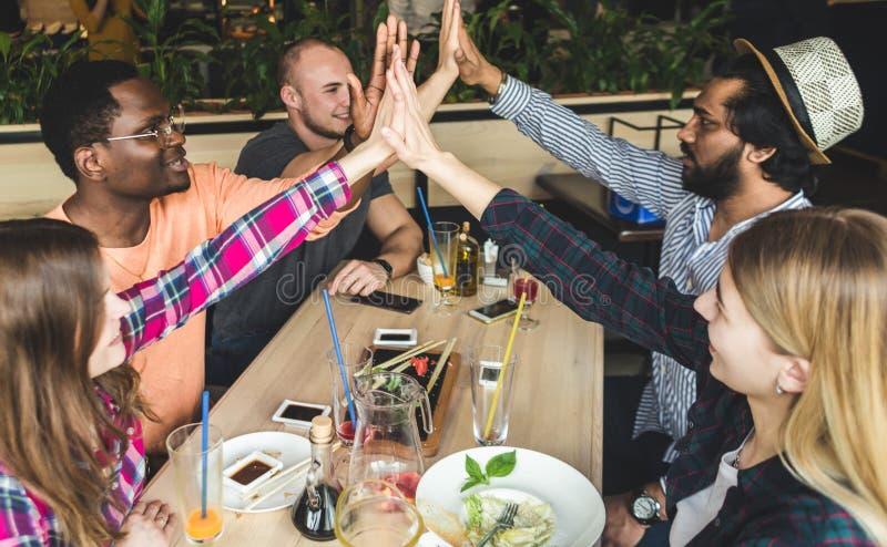 Ontmoet jonge aantrekkelijke mensen in de koffie De vrienden babbelen, hebben pret, drinken cocktails en eten stock afbeelding
