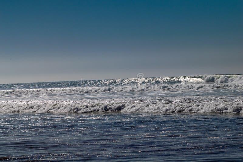 Ontruim blauwe hemel en zonlicht met de golven die van de Atlantische Oceaan op zandstrand verpletteren zonder mensen in Agadir,  royalty-vrije stock afbeeldingen