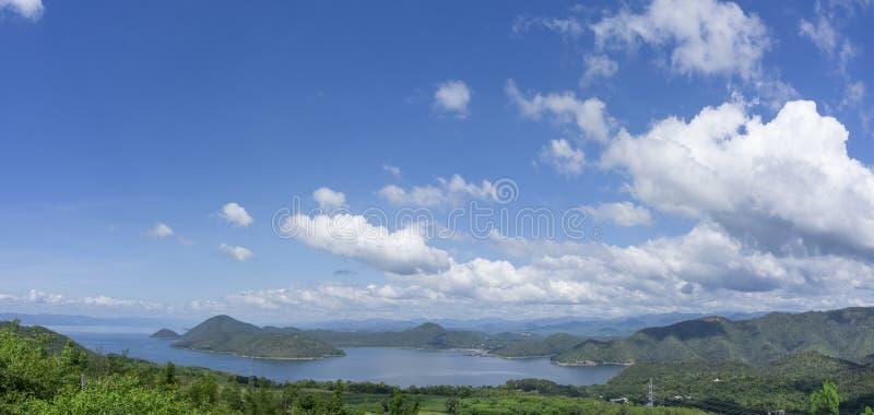 Ontruim blauwe hemel witte wolken, bomen, natuurlijke grasbomen rond het Srinakarin-Reservoir, Kanchanaburi, Thailand stock afbeelding