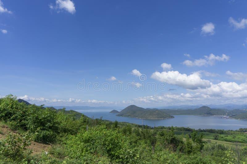 Ontruim blauwe hemel witte wolken, bomen, natuurlijke grasbomen rond het Srinakarin-Reservoir, Kanchanaburi, Thailand stock foto's