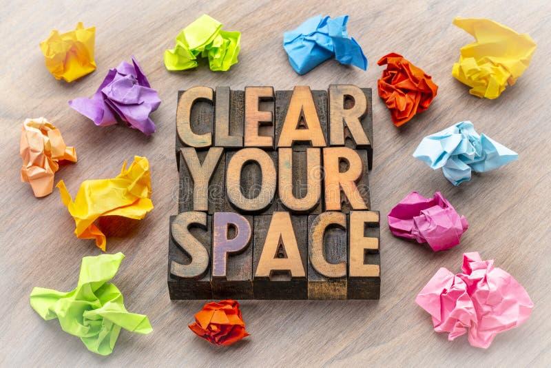 Ontruim uw ruimte - woordsamenvatting in houten type stock afbeelding
