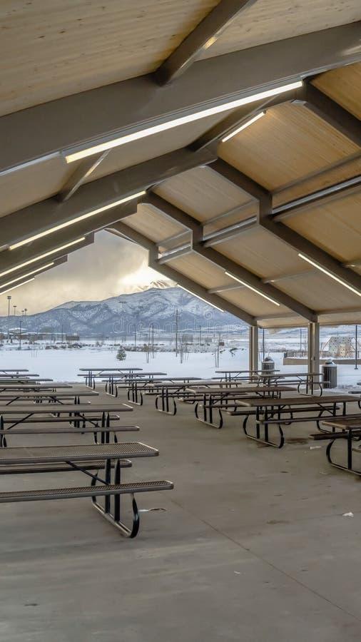 Ontruim Verticaal Behandeld die picknickgebied en speelplaats bij een park met sneeuw in de winter wordt bedekt royalty-vrije stock afbeelding
