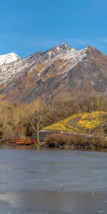 Ontruim Verticaal Ijzig meer en opvallende sneeuw afgedekte berg tegen trillende blauwe hemel in de winter stock fotografie