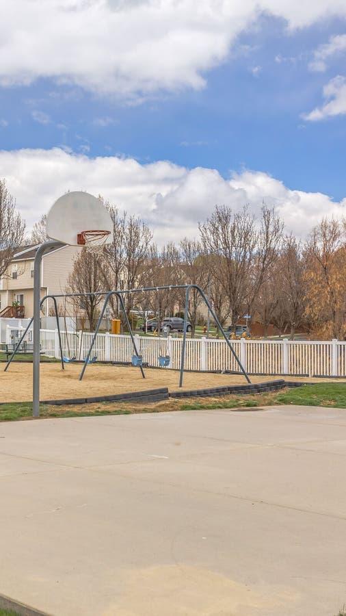 Ontruim Verticaal Speelplaats en basketbalhof tegen huizen en blauwe hemel met gezwollen wolken royalty-vrije stock afbeeldingen