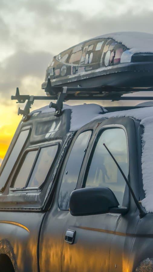 Ontruim Verticaal Zwart voertuig met een van het dakrek en dak ladingsdrager die in de winter wordt bekeken stock afbeelding