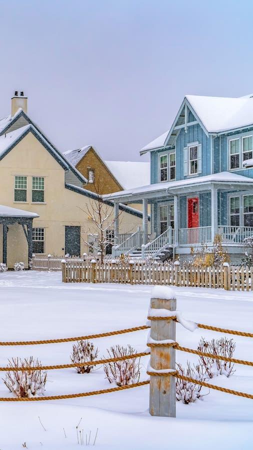 Ontruim Verticale Aanbiddelijke huizen voorbij een kabelomheining op de sneeuw behandelde grond in de winter stock foto