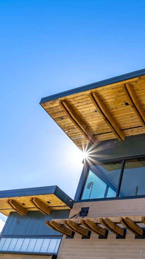 Ontruim Verticale Buitenkant van een gebouw met rode bakstenen muur en vlak dak tegen levendige blauwe hemel stock afbeelding