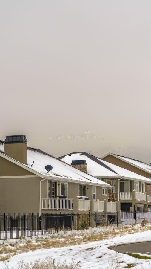 Ontruim Verticale die Voorgevel van huizen tegen sneeuw afgedekte berg en witte hemel in de winter worden bekeken royalty-vrije stock foto