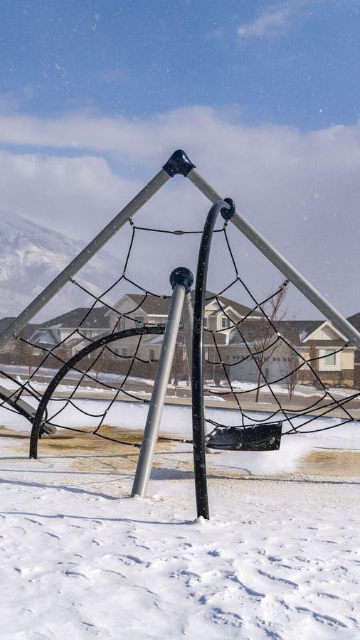 Ontruim Verticale klimrekken op een speelplaats die met sneeuw op een zonnige de winterdag wordt bedekt stock afbeeldingen