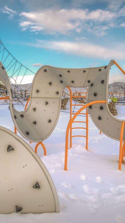 Ontruim Verticale klimrekken op een speelplaats met de grond die met sneeuw in de winter wordt behandeld royalty-vrije stock afbeeldingen