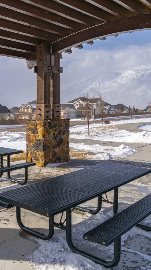 Ontruim Verticale Lijsten en banken binnen een paviljoen bij een sneeuwpark op een zonnige de winterdag royalty-vrije stock fotografie