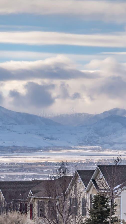 Ontruim Verticale Opvallende die berg met sneeuw onder een bewolkte blauwe hemel in de winter wordt bedekt royalty-vrije stock foto's