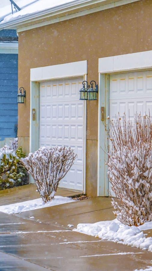 Ontruim Verticale Witte die garagedeuren van huizen in Dageraad Utah in de winter wordt bekeken stock afbeelding