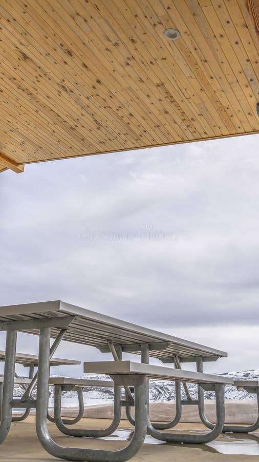 Ontruim Verticale Witte lijsten en banken binnen een paviljoen dat met sneeuw in de winter wordt omringd royalty-vrije stock fotografie