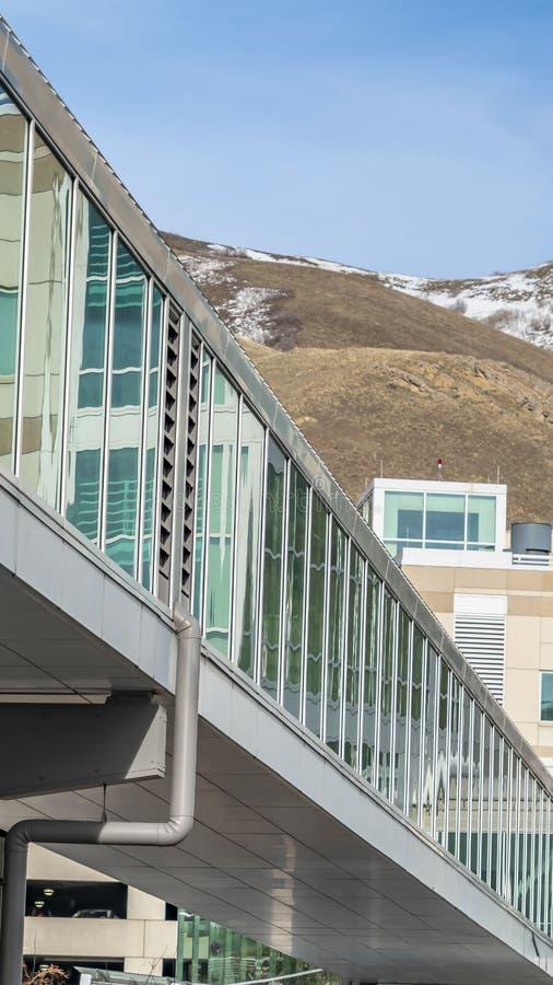 Ontruim Verticale Zonnige dagmening van de moderne bouw buiten met een ommuurd glas skybridge royalty-vrije stock afbeelding