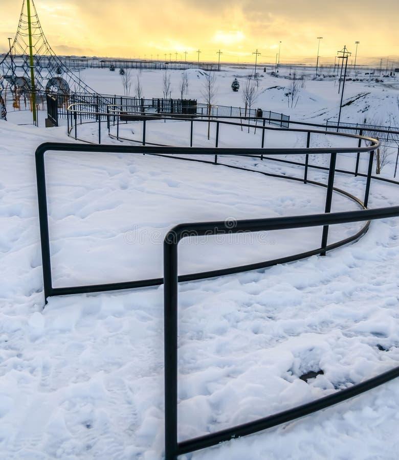 Ontruim Vierkant Kabel klimrek en buigende weg met leuningen op een park in de winter stock fotografie