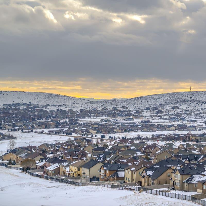 Ontruim Vierkant Panorama van huizen op een berg die met sneeuw tijdens wintertijd met een laag wordt bedekt stock foto