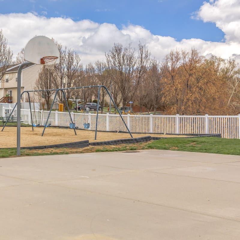 Ontruim Vierkant Speelplaats en basketbalhof tegen huizen en blauwe hemel met gezwollen wolken royalty-vrije stock afbeeldingen