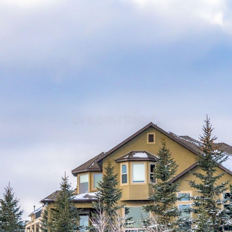 Ontruim Vierkante Buitenkant van een elegant huis tegen blauwe hemel met gezwollen wolken in de winter stock foto's