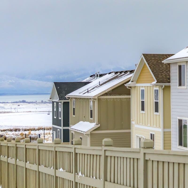 Ontruim Vierkante Buitenkant van huizen binnen een houten omheining tegen een sneeuwlandschap in de winter stock fotografie