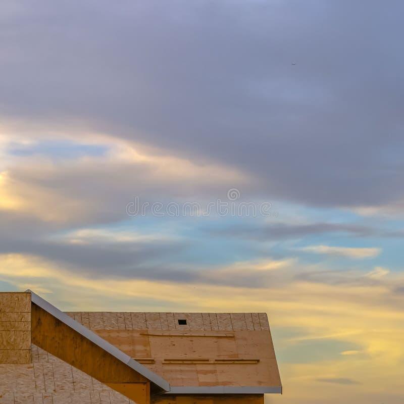 Ontruim Vierkante Dichte omhooggaand van het dak van een nieuw die huis bij een bouwwerf bij zonsondergang wordt bekeken stock foto