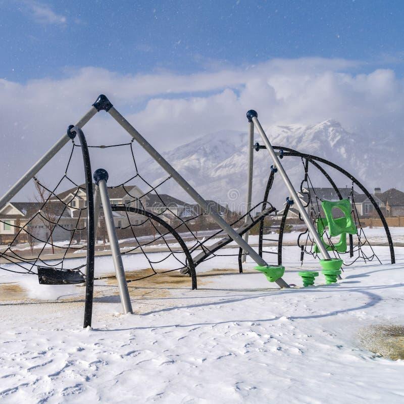 Ontruim Vierkante die klimrekken op een speelplaats met sneeuw op een zonnige de winterdag wordt bedekt stock fotografie