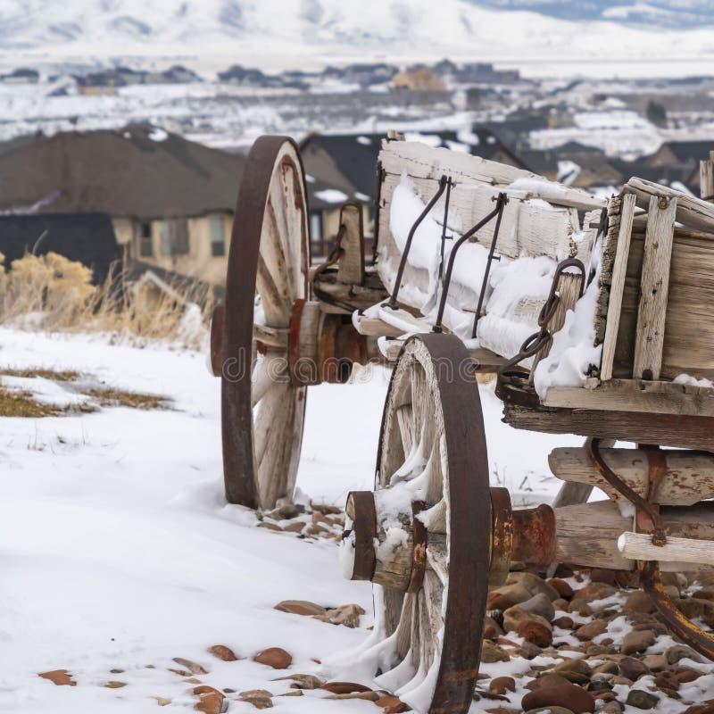 Ontruim Vierkante Doorstane houten wagen met kettingen en roestig die wiel in de winter worden bekeken stock foto