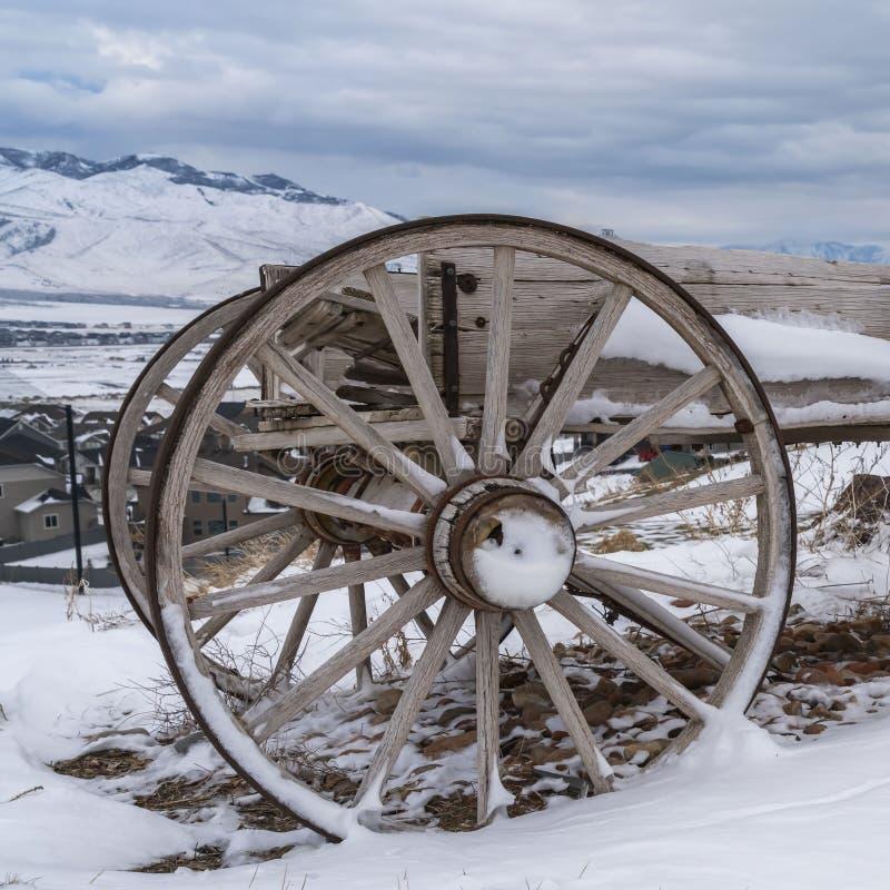 Ontruim Vierkante Houten kar op een heuvel met een mening van sneeuw afgedekte berg en wolk gevulde hemel royalty-vrije stock foto's