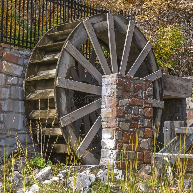 Ontruim Vierkante Houten waterwiel en goot bij een grasrijke die vijver op een zonnige dag wordt bekeken royalty-vrije stock foto