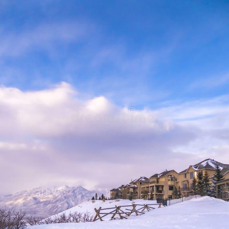 Ontruim Vierkante Huizen die een toneelsneeuw afgedekte berg en een levendige blauwe hemel met wolken overzien royalty-vrije stock foto