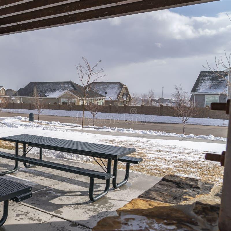 Ontruim Vierkante Lijsten en banken binnen een paviljoen bij een sneeuwpark op een zonnige de winterdag royalty-vrije stock foto