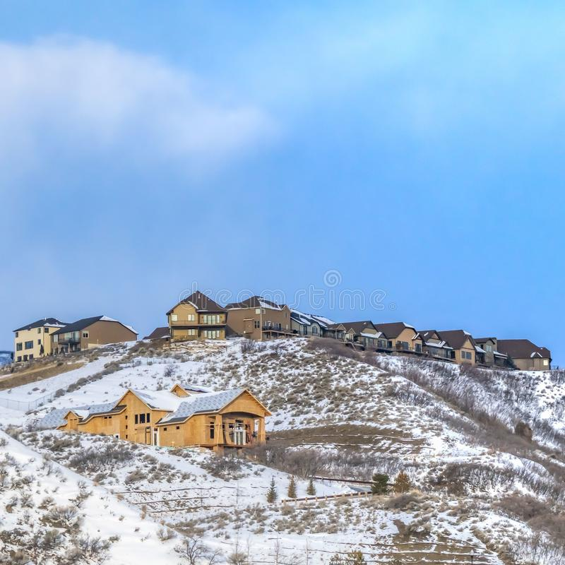 Ontruim Vierkante Mooie huizen die bovenop een berg worden gebouwd die met sneeuw in de winter wordt behandeld stock foto's