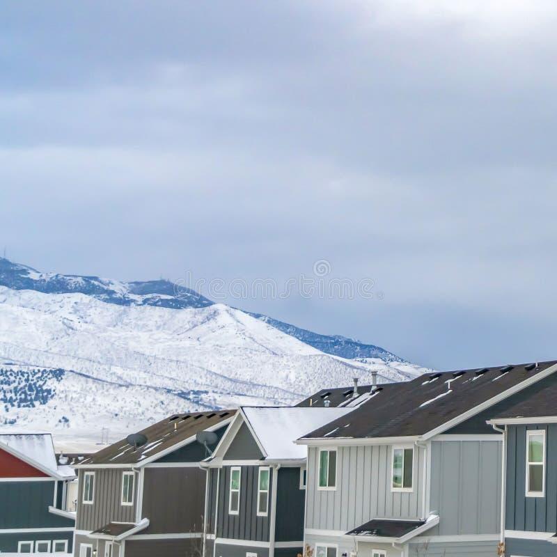 Ontruim Vierkante Rij van huizen tegen sneeuw behandelde berg onder de wolk gevulde hemel stock afbeeldingen