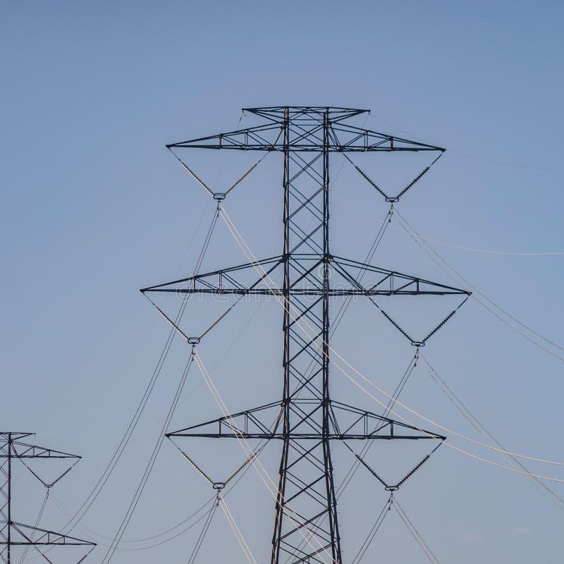 Ontruim Vierkante Rij van lange nutstorens tegen lichtblauwe hemel met gezwollen wolken royalty-vrije stock fotografie
