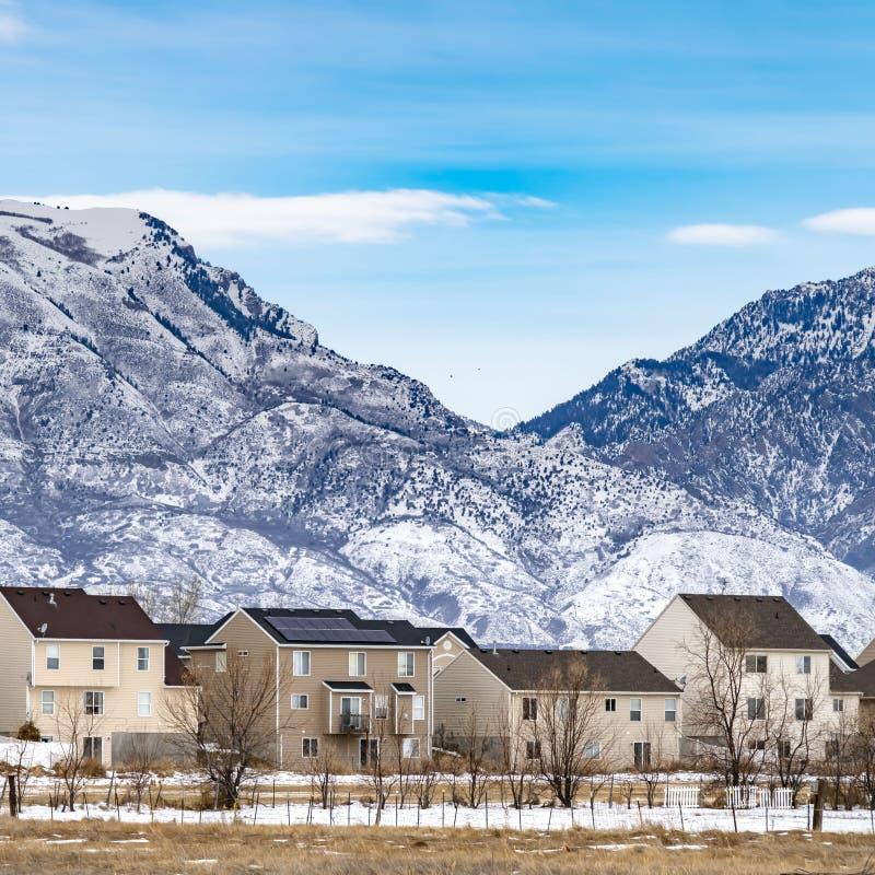 Ontruim Vierkante Rij van mooie huizen tegen een ruwe die berg met sneeuw in de winter wordt bestrooid royalty-vrije stock fotografie
