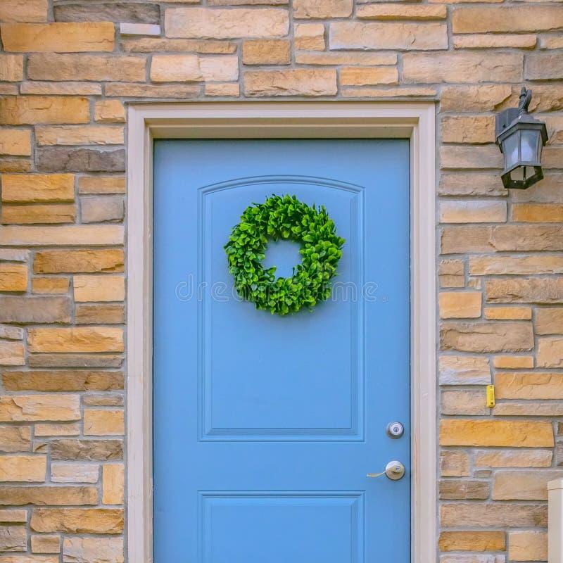 Ontruim Vierkante Voorgevel van een huis met blauwe voordeur en lamp op de steenbakstenen muur stock afbeelding