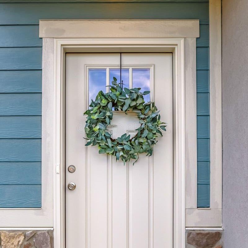 Ontruim Vierkante Voorgevel van een huis met een eenvoudige bladkroon die op de witte voordeur hangen stock foto