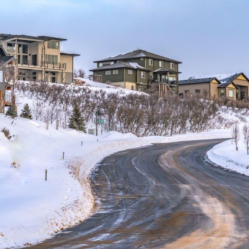 Ontruim Vierkante Weg die de winden op een heuvel met poederachtige sneeuw op een zonnige de winterdag bedekten royalty-vrije stock foto