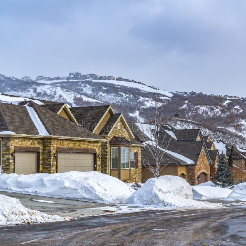 Ontruim Vierkante Weg die door een sneeuw behandeld landschap met mooie huizen in de winter winden royalty-vrije stock afbeelding