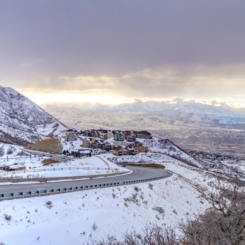 Ontruim Vierkante Weg die langs een berg buigen die met sneeuw tegen bewolkte hemel in de winter met een laag wordt bedekt stock afbeelding