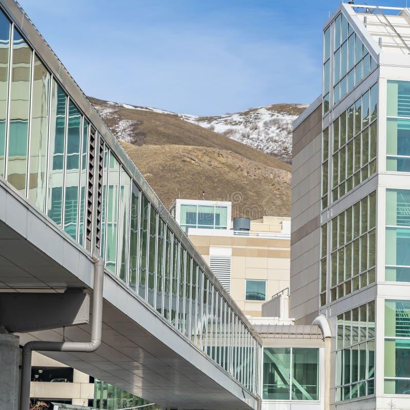 Ontruim Vierkante Zonnige dagmening van de moderne bouw buiten met een ommuurd glas skybridge stock foto's